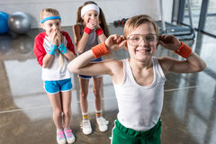 Förtjusande ungar i sportswearen som omkring bedrar på konditionstudion arkivbild
