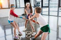 Förtjusande ungar i sportswearutbildning med rep på konditionstudion royaltyfria foton