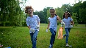Förtjusande ungar som hoppar, medan ställa upp som frivillig och göra ren utomhus stock video