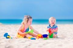 Förtjusande ungar som spelar på stranden Arkivfoton