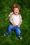 Förtjusande unge som skrattar på gräs Arkivbild