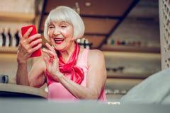 Förtjust åldrig kvinna som använder hennes moderna grej royaltyfri bild