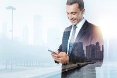 Förtjust affärsman som får ett meddelande på hans smarta telefon Fotografering för Bildbyråer