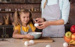 Förtjust dottermatlagning med hennes moder i köket fotografering för bildbyråer