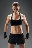 Förtjust flicka som poserar i sportswear på en grå bakgrund fotografering för bildbyråer