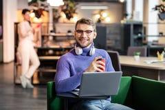 Förtjust kontorsarbetare som har avbrottet med kaffe arkivbild