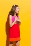 Förtjust liten flicka med händer på bröstkorg Royaltyfri Bild