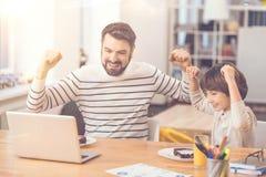 Förtjust lycklig fader och son som rymmer upp deras händer arkivbilder