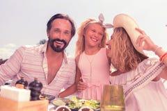 Förtjust lycklig familj som tillsammans sitter på tabellen arkivfoto
