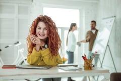 Förtjust lycklig ung kvinna som tycker om hennes arbete arkivfoto