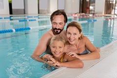 Förtjust lyckligt enigt familjanseende i vattnet royaltyfri foto