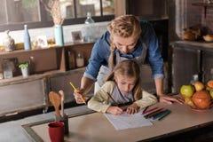 Förtjust moderteckning med hennes dotter i köket Arkivfoton