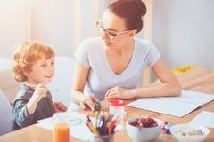 Förtjust moderteckning med hennes litet barnson tillsammans royaltyfri fotografi