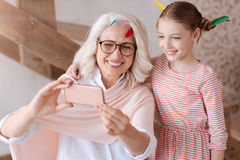 Förtjust positiv farmor och sondotter som tar ett foto royaltyfria foton