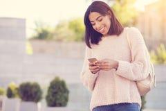 Förtjust positiv kvinna som använder hennes mobiltelefon arkivfoton