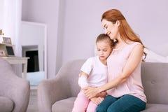 Förtjust positiv kvinna som ger en kram till hennes dotter arkivbild