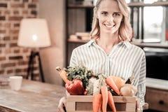 Förtjust positiv kvinna som rymmer en ask med grönsaker Royaltyfri Foto
