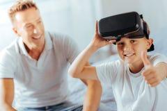 Förtjust positiv pojke som är lycklig om exponeringsglas 3d Arkivbild