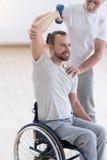 Förtjust rörelsehindrad man som övar med hans assistent i idrottshallen Arkivfoto
