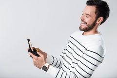 Förtjust skäggig man som skrattar och använder bärbar gamepad royaltyfri fotografi