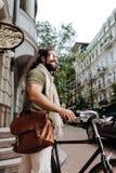 Förtjust stiligt mananseende nära hans cykel Royaltyfri Bild