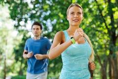 Förtjust trevlig kvinna som joggar i morgonen arkivfoton
