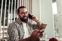 Förtjust upptagen man som har en telefonkonversation arkivfoton