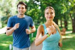 Förtjusta glade par som tillsammans joggar i parkera royaltyfri foto