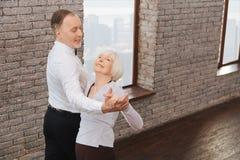 Förtjusta pensionärer som valser i dansstudion Arkivbilder