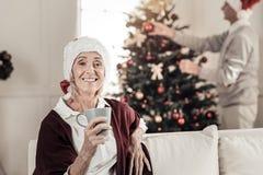 Förtjusta pensionärkvinnlign som den har, vilar hemma Arkivfoto