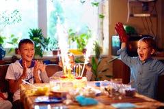 Förtjusta ungar som blåser stearinljus på kakan, medan fira ett födelsedagparti hemma royaltyfri bild