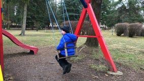 Förträningsålderpojken på gunga i parkerar bakifrån Ung pojke som bara spelar på gunga i lekplats i vinter arkivfilmer