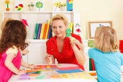 Förträningsbarn i klassrumet med läraren Arkivfoton