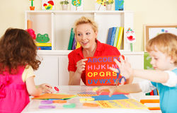 Förträningsbarn i klassrumet med läraren arkivbilder