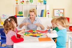 Förträningsbarn i klassrumet med läraren Arkivbild