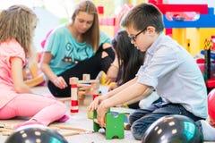 Förträningspojke som samarbetar med ungar under vägledning av kindergar royaltyfri bild
