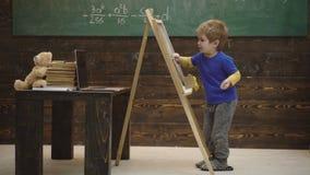 Förträningsutbildning Little Boy teckning med krita på svart tavla Utbildning för tidig barndom och spelabegrepp stock video