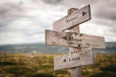 Förtroende-, hopp- och förälskelsetext på trävägvisaredet fria i natur royaltyfri bild