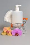 Förtrogen stelnar den plast- flaskan för utmatarepumpen, sanitetsbinda i handkärra med orkidéblommor royaltyfri foto