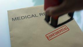 Förtroliga sjukdomshistorier och att stämpla skyddsremsan på mapp med viktiga dokument stock video