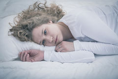 Förtvivlanflicka som ligger i säng Arkivbilder