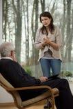 Förtvivlanflicka som talar med psykiatern Royaltyfri Bild