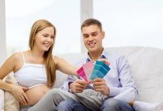 Förvänta föräldrar som väljer färg för barnkammare Royaltyfria Bilder