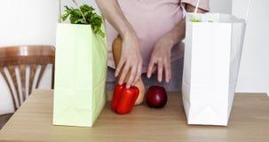 Förvänta kvinnan ta ut grönsaker från shoppingpåse stock video