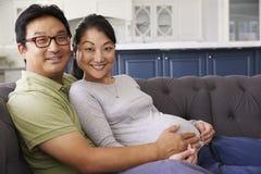 Förväntansfulla par som kopplar av på Sofa At Home Together royaltyfri foto