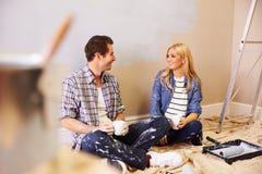 Förväntansfulla par som tar en avbrottsstund som dekorerar barnkammaren arkivbild
