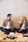 Förväntansfulla par som tar en avbrottsstund som dekorerar barnkammaren fotografering för bildbyråer