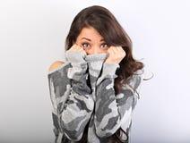 Förvåna kvinnan med stora öppna ögon som döljer hennes framsida inom den gråa varma vintersweatern på blå bakgrund closeup arkivfoton