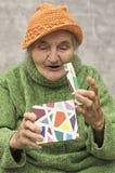 Förvånad äldre kvinna, når att ha öppnat gåvaasken Arkivbild
