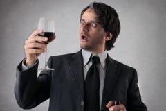 Förvånad affärsman med ett exponeringsglas av vin Royaltyfri Bild